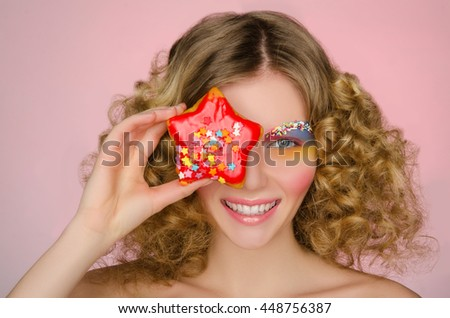 smiling woman with donut in face on pink background