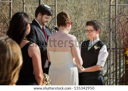 Smiling woman with glasses holding hands with bride - stock photo