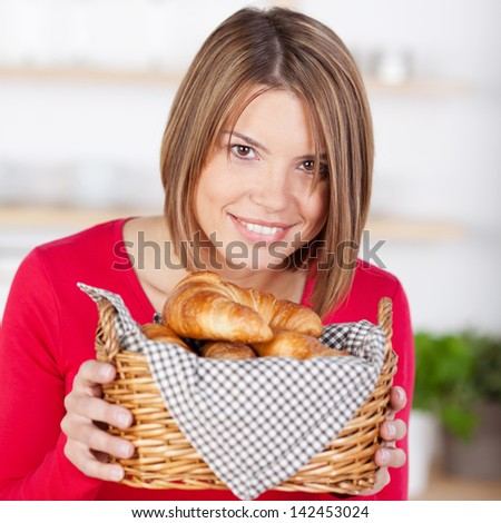 Smiling woman with golden fresh baked croissants in a wicker basket in her hands - stock photo