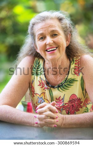 Smiling woman with gray hair and folded hands - stock photo