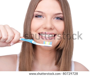 smiling woman with great teeth holding tooth-brush, isolated on white background