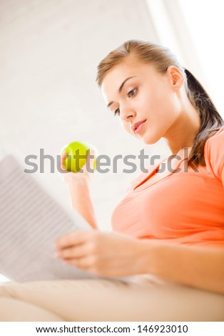 smiling woman with green apple reading magazine at home - stock photo
