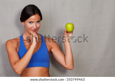 Smiling woman with hand on chin and holding apple against grey texture background