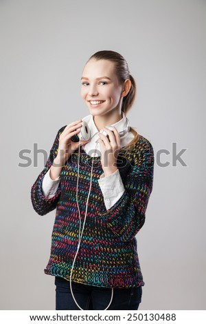 Smiling woman with headphones listening music on player. Music teenager girl portrait against isolated grey background - stock photo
