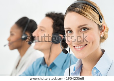 Smiling Woman With Headsets Working With Other Colleague In Call Center - stock photo