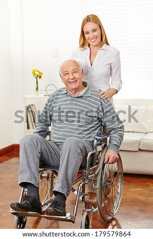Smiling woman with her old senior father in a wheelchair at home - stock photo