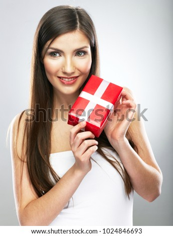 Smiling woman with long hair holding red gift box. Isolated studio portrait.