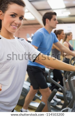 Smiling woman with other people stepping on  step machines in gym - stock photo