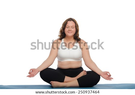 Smiling woman with overweight practices yoga on blue mat