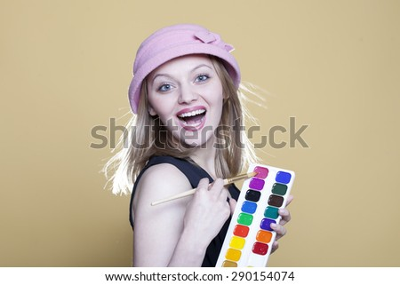 Smiling woman with paint and brush on beige background - stock photo