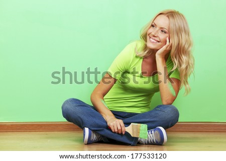 Smiling woman with painting brush sitting near the wall - stock photo
