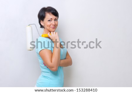 Smiling woman with painting roller - stock photo