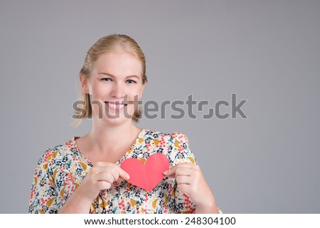 Smiling woman with paper heart as a symbol of love - stock photo