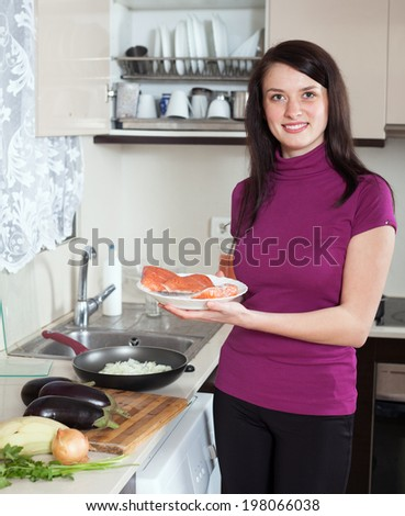Smiling woman with raw salmon fish with vegetables at home kitchen