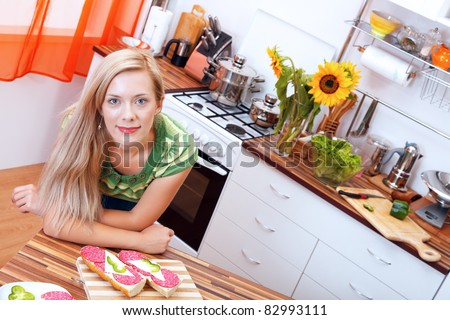 Smiling woman with sandwiches in the kitchen