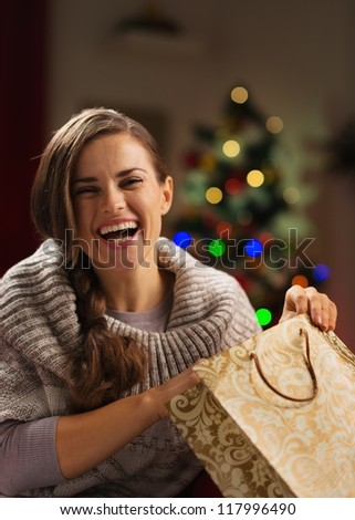 Smiling woman with shopping bag in front of Christmas tree - stock photo