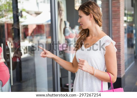 Smiling Woman with shopping bag pointing the window at the shopping mall - stock photo
