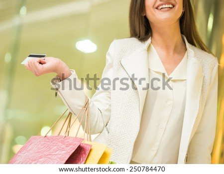Smiling woman with shopping bags in shopping mall with credit card is looking at the camera. Sales. Shopping Center. - stock photo