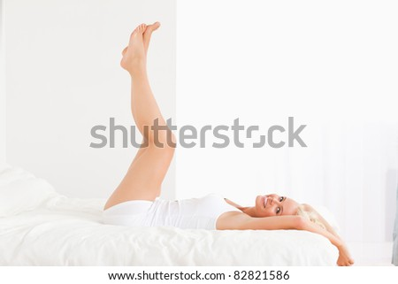 Smiling woman with the legs up while lying on her bed - stock photo