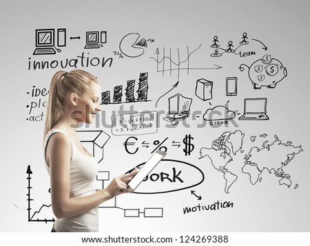 Smiling woman with touchpad and business scheme - stock photo