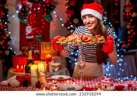 Smiling woman with turkey garnished with potato and garnet dressed with Christmas hat on festive light background - stock photo
