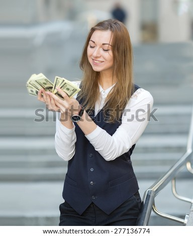Smiling woman with us dollar money. Business woman holding money. Woman and money. Young business woman holding a lot of US hundred dollar bills. Business woman has earned a good amount of dollars. - stock photo
