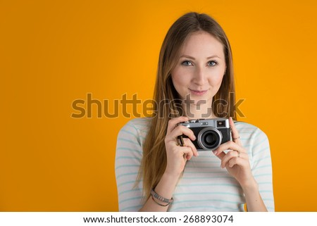 Smiling woman with vintage camera close up against orange background.  - stock photo