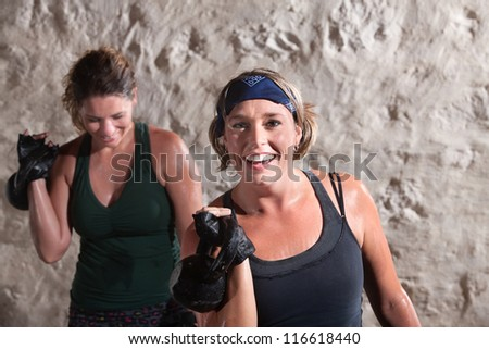 Smiling woman with workout partner lifting weights - stock photo