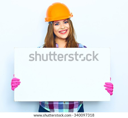 Smiling woman worker builder hold big sign board against white background. Building helmet. Pink glow. - stock photo