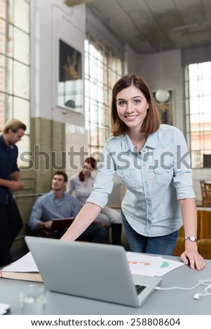 Smiling woman working in a design studio standing at her desk with a laptop and large paper drawing while her colleagues work in the background - stock photo