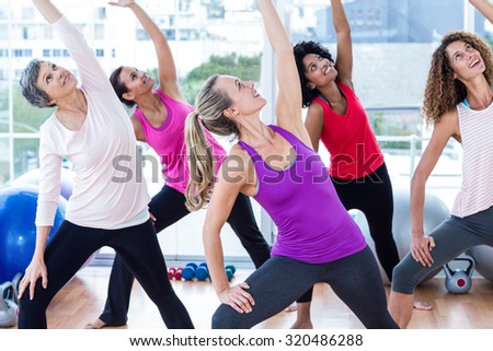 Smiling women exercising with arms raised while looking up in fitness studio - stock photo