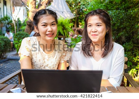 Smiling women friends with hot drink using laptop in cafe for start up business