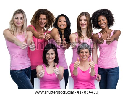 Smiling women in pink outfits showing thumbs up for breast cancer awareness on white background - stock photo