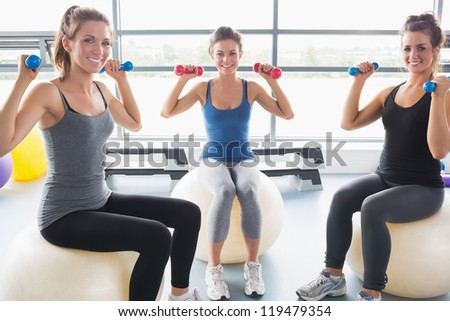 Smiling women lifting weights on an exercise ball in a gym - stock photo