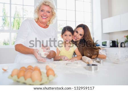Smiling women of a family baking together in the kitchen