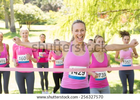 Smiling women running for breast cancer awareness on a sunny day - stock photo