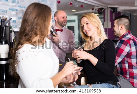 Smiling women talking at a bar and holding glasses with cocktails in their hands. Bartender is mixing a drink in a shacker for a man on a background