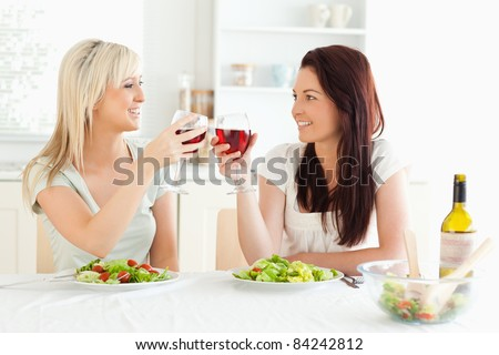 Smiling Women toasting with wine in a kitchen - stock photo