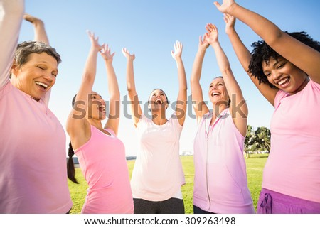 Smiling women wearing pink for breast cancer and cheering in parkland - stock photo