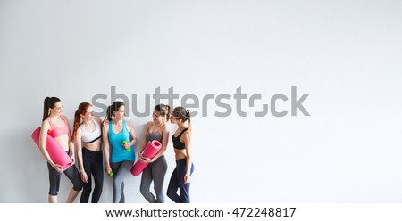 Smiling women yoga / fitness class. Young athletic women friends with yoga mats and dumbbells on a white background.