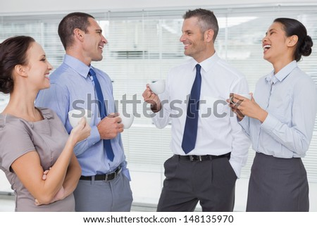 Smiling work team during break time in bright office - stock photo