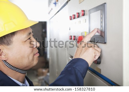 Smiling worker checking controls in a gas plant, Beijing, China - stock photo