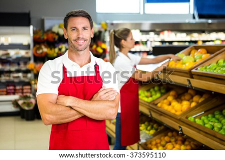 Smiling worker in front of colleague in grocery store - stock photo