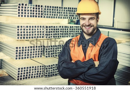smiling worker in protective uniform and protective helmet in production hall in front of steel sheet metal profiles - toned image, retro film filtered in instagram style - stock photo