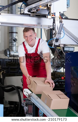 Smiling worker packing boxes on conveyor belt