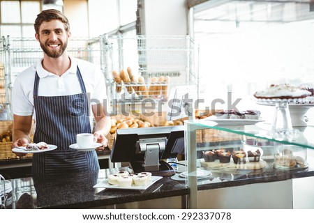 Smiling worker prepares breakfast at the bakery - stock photo