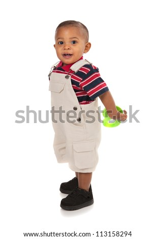 Smiling 1-year old baby boy standing Full Body Length Portrait holding toy on isolated background - stock photo
