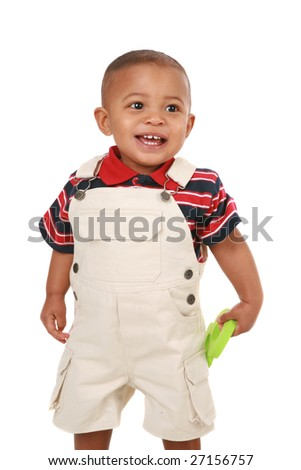 Smiling 1-year old baby boy standing holding toy on isolated background