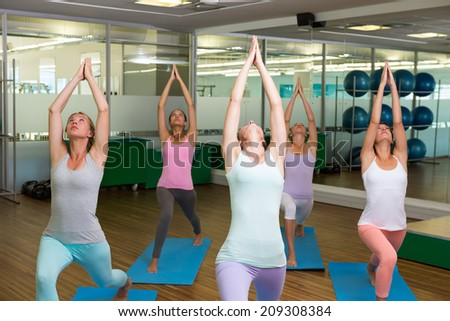 Smiling yoga class in fitness studio at the leisure center - stock photo