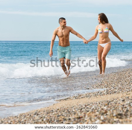 Smiling young adult couple having fun at seashore in sunny day - stock photo